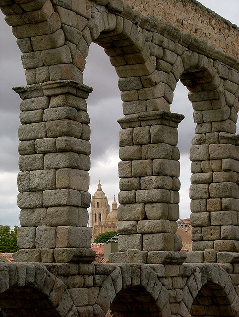 View of the cathedral through the arches of the Roman aqueduct in Segovia, Spain
